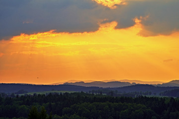 The sky at sunset over forests and forested mountains