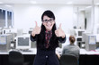 Businesswoman thumbs up at office