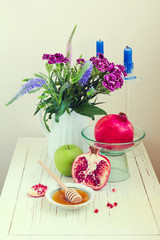 Honey, apple, pomegranate and flowers on wooden white table