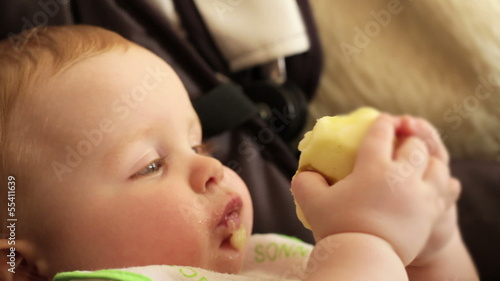 Portrait of baby boy eating green apple, close up