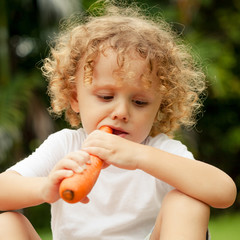 Happy little boy holding a carrots. Concept of healthy food.