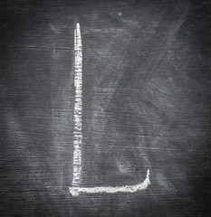 L - letter written on black chalkboard.
