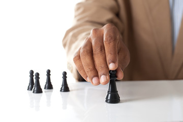 Business man moving chess figure with team behind - strategy or