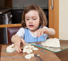 Cute little girl learning to make the dough figurines