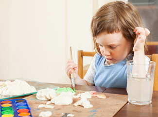 The little girl paints the dough figurines