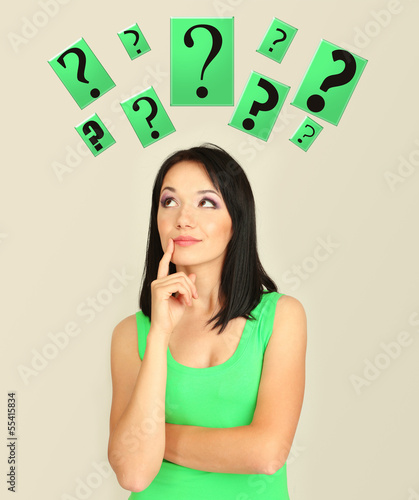 Girl thinking surrounded by question marks on beige background