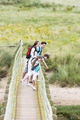 Family Walking Along Wooden Bridge