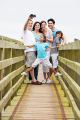 Multi Generation Family Walking On Bridge Taking Photo