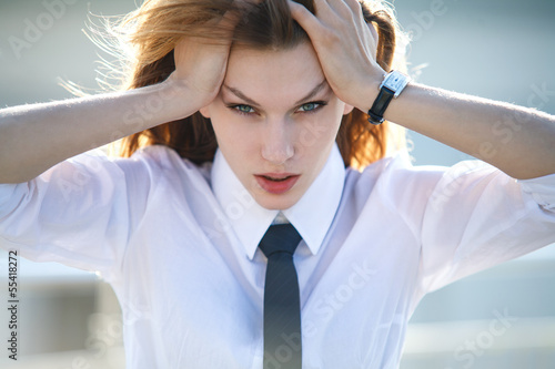 Distressed young woman holds her head with both hands