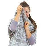 Smiling young woman hiding in sweater neckline poster