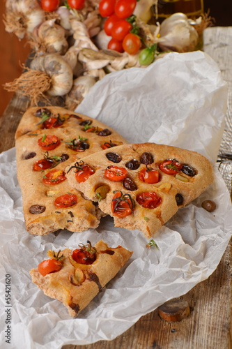 Focaccia with tomato, fresh garlic and black olives.