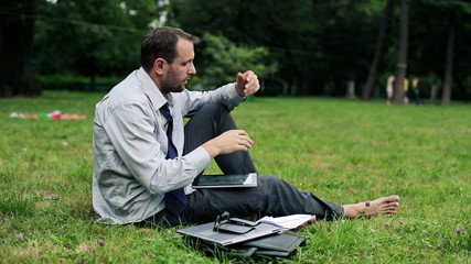 Tired, overworked businessman with documents in the park
