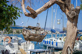 Wooden toy boat on a tree in the harbor of Poros island, Greece
