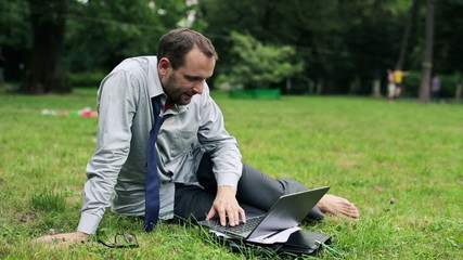 Businessman working on laptop in the park