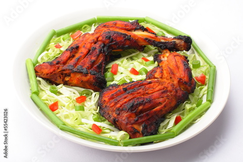 Tandoori chicken on plate with fresh vegetables