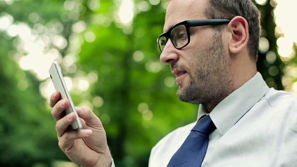 Businessman sending sms, texting in the park