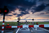 closed rail crossing at sunrise and windmill
