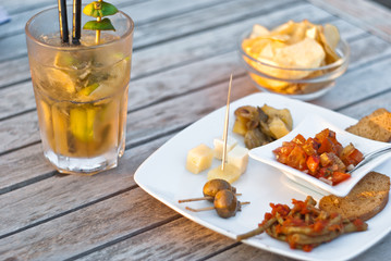mojito cocktail with snacks on wooden table