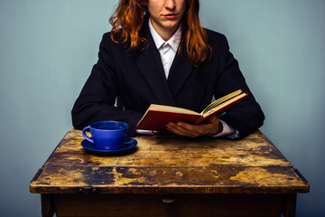 Businesswoman reading and having coffee