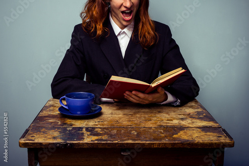 Businesswoman reading a naughty book and having coffee