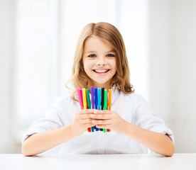 girl showing colorful felt-tip pens