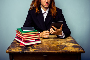 Woman in suit with digital reader and stack of books