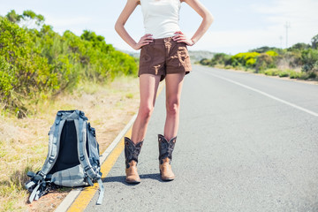 Backpacking woman on the roadside posing