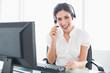 Happy call centre agent sitting at her desk on a call