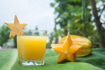 Starfruit and Starfruit juice on a banana leaf.