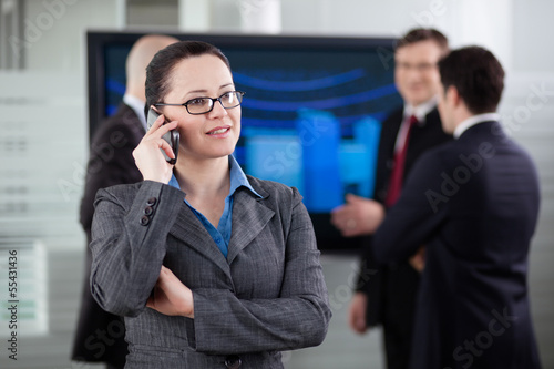Businesswoman talking on the phone in the conference room. Colle