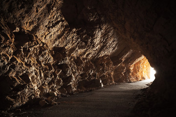 Empty road goes through the cave with glowing end
