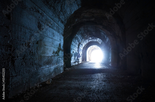 Foto op Plexiglas Tunnel Blue glowing exit from dark abandoned tunnel
