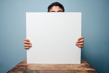 Man at desk hiding behind a white board