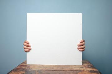 Hands holding white board at desk