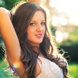 Beautiful brunette girl outdoors backlight portrait.