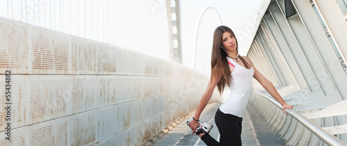 Panoramic image of woman stretching her legs outdoors in modern