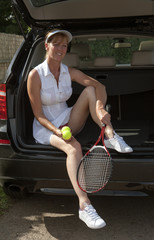 Female tennis player sitting in trunk of car