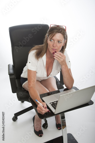 Female office worker and computer deep in thought