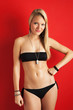 Beautiful blonde woman portrait with black bikini on red backgro