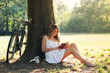 Beautiful young woman portrait reading a book under a tree with