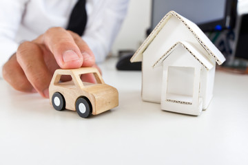 Wooden car and home on a table.