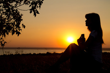 silhouette of a girl reading at sunset