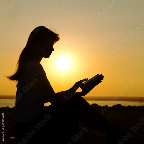 silhouette of a girl with a book in hands at sunset