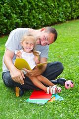 papà e figlia leggono in giardino