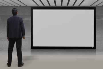 Businessman looking at blank TV screen