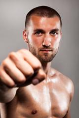 Attraktiver Sportler hält die Faust nach vorne