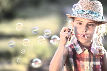 girl in a hat lets soap bubbles