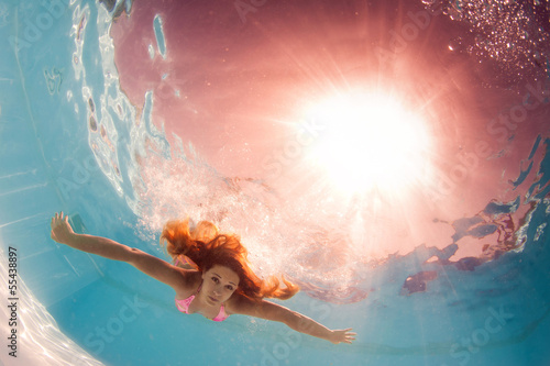 Underwater woman back light portrait in swimming pool.