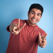 Happy man portrait with victory sign against blue background.