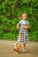 little girl is riding a scooter